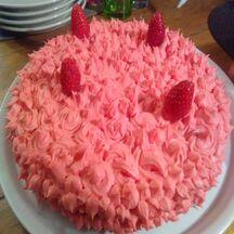 Gâteau magique au chocolat blanc sur un lit de fraises, décoré de crème au beurre