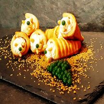 Cornets à la chantilly de parmesan parsemés de pignons de pin et accompagnés de perles de basilic